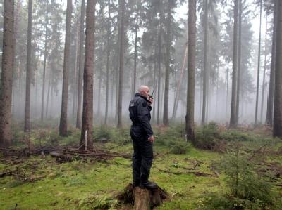 Ein Polizeibeamter gibt an der Bahnstrecke zwischen Lüneburg und Dannenberg eine Meldung über Funk an seine Einsatzzentrale.