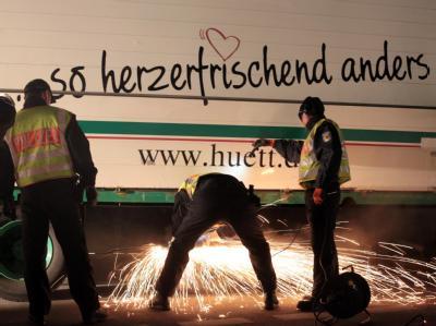 Polizeibeamte versuchen, Greenpeace-Aktivisten aus dem Laderaum des getarnten Lasters herauszubekommen.