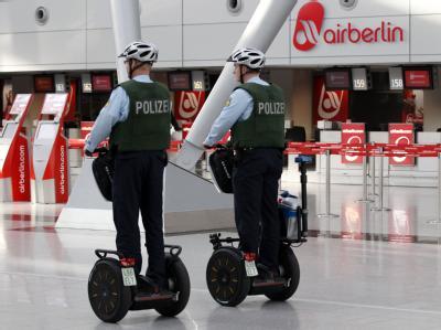 Bundespolizisten fahren in Düsseldorf im Flughafenterminal auf Sagways an einem Schalter der Fluggesellschaft Air Berlin vorbei.