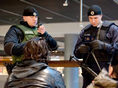 Zwei bewaffnete Bundespolizisten führen im Hauptbahnhof in Berlin eine Ausweiskontrolle von zwei Reisenden durch.