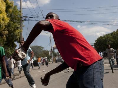 Ein Haitianer schleudert in Port au Prince einen Stein auf die dort stationierten UN-Blauhelme.