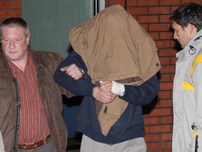 Der mutmaßliche Doppelmörder wird von Polizeibeamten abgeführt.
