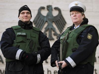 Polizisten stehen in kugelsicheren Westen und mit Maschinenpistole vor dem Auswärtigen Amt in Berlin.