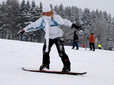 Ein Mädchen fährt in Winterberg mit einem Snowboard einen Hang hinunter. Tausende Spaziergänger und Wintersportler haben das erste Adventswochenende zu Ausflügen genutzt.