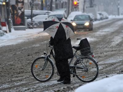 Erschwerte Bedingungen: Eine Frau schiebt am Montagmorgen ihr Fahrrad über eine verschneite Kreuzung in München.