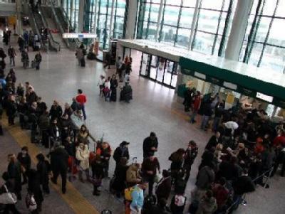 Passagiere, die auf einen Flug nach Spanien warten, vor dem Check-In am römischen Flughafen Leonardo da Vinci.