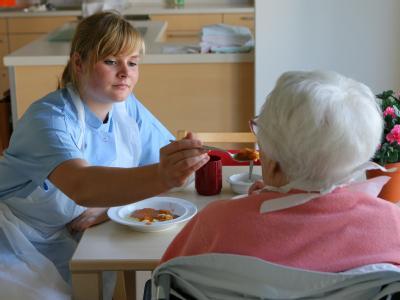In einer Seniorenwohnanlage in Rostock hilft eine Altenpflegerin einer Bewohnerin beim Essen. Nach Zahlen des Statistischen Bundesamts fehlen in 15 Jahren voraussichtlich 112000 Pfleger in Vollzeitanstellung.