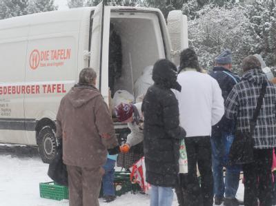 Vor der mobilen Ausgabestelle für Lebensmittel der Magdeburger Tafel stehen Bedürftige in einer Reihe.