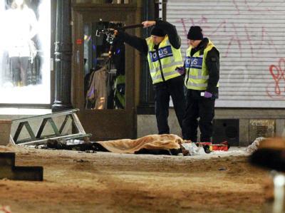 Polizisten untersuchen die Überreste des Selbstmordattentäters.
