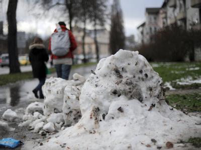Die Reste eines Schneemanns liegen in Kassel auf dem Bürgersteig. Nach dem großen Auftauen kommt die Kälte jetzt zurück.