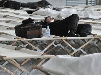 Passagiere auf dem Flughafen Frankfurt schlafen auf Feldbetten.