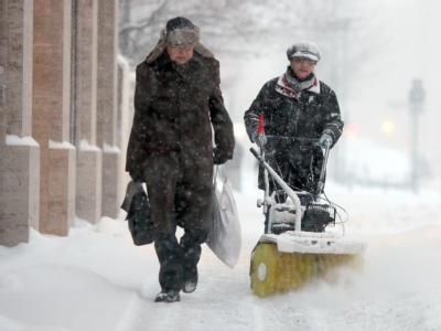 Eine Helferin befreit im Berliner Stadtteil Mitte den Gehweg vom Schnee.