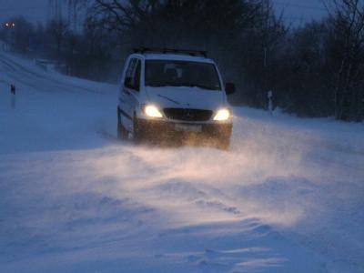 Ein Auto auf der schneebedeckten B203 in Schleswig-Holstein.