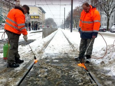 Mitarbeiter der Kölner Verkehrsbetriebe enteisen die Gleise auf der Aachener Straße in Köln. Im Nahverkehr läuft immer noch nicht alles rund, aber die Verkehrslage hat sich beruhigt.