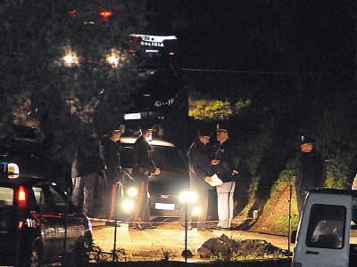 Polizisten untersuchen den Ort des fünffachen Mordes.