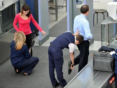 Luftsicherheitsbeauftragte kontrollieren am Flughafen in München Fluggäste.