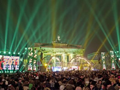 Tausende Besucher verfolgen vor dem Brandenburger Tor in Berlin auf der Straße des 17. Juni die Open-Air-Silvesterparty. Auf der 2,2 Kilometer langen Silvester-Partymeile zwischen Brandenburger Tor und Siegessäule sollen rund eine Million Menschen gefeier
