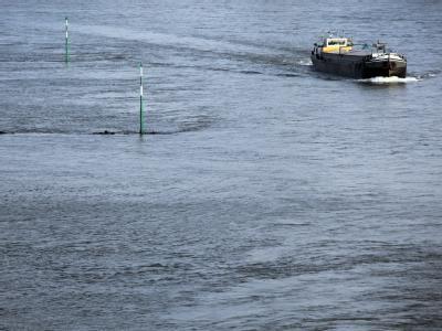 Ein Schiff fährt an überfluteten Rheinbuhnen in Düsseldorf vorbei.