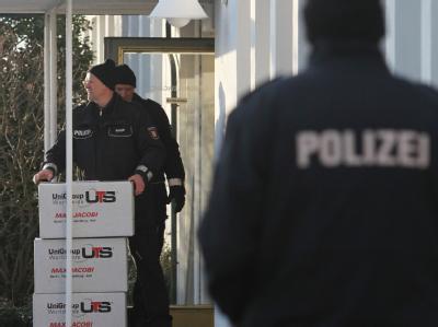 Polizeibeamte tragen Kisten mit beschlagnahmten aus dem Firmensitz der Firma Harles und Jentzsch in Uetersen.