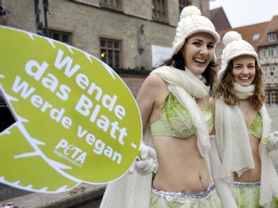 Aktivistinnen der Tierrechtsorganisation PETA werben nur mit einem Bikini aus Salatblättern, Schal, Mütze und Handschuhen bekleidet, in Göttingen für vegane Ernährung.