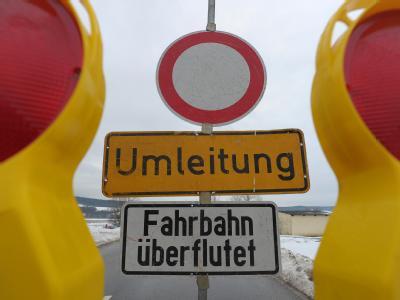 Warnschild vor einer überfluteten Landstraße zwischen Busendorf und Gleusdorf in der Nähe von Bamberg.