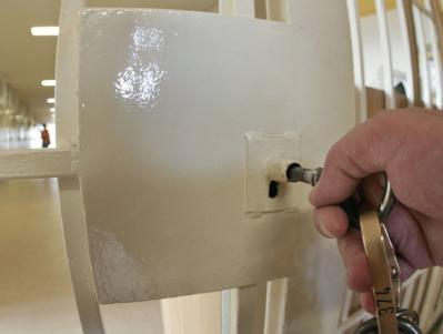 Ein Beamter verschließt die Tür eines Gefängnistrakts.