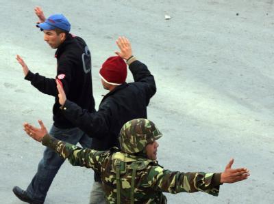 Ausnahmezustand in Tunis: Mit erhobenen Händen bringen sich Passanten in Sicherheit.