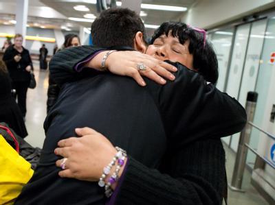 Eine aus Tunesien rückkehrende Frau umarmt in Stuttgart im Flughafen ihren Sohn.