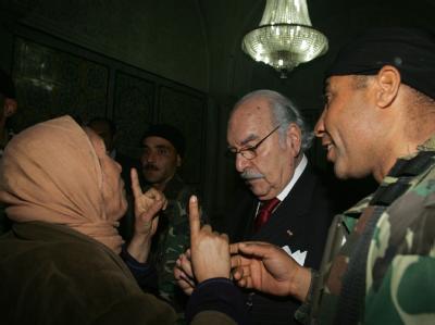 Eine Frau spricht mit Übergangspräsident Foued Mebaaza.
