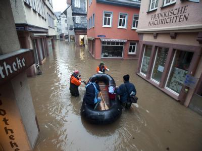 Feuerwehrleute bugsieren am Montagmorgen in Wertheim am Main ein Schlauchboot mit einer Frau durch die überfluteten Gassen der Innenstadt. Die Einsatzkräfte bereiteten sich hier auf die zweite Hochwasserwelle innerhalb einer Woche vor.