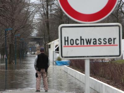 Hochwasser-Warnschild auf einem Fußweg bei Magdeburg.