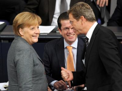 Bundeskanzlerin Angela Merkel, Verteidigungsminister Karl-Theodor zu Guttenberg und Außenminister Guido Westerwelle unterhalten sich im Bundestag.