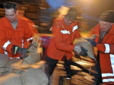 Mit Sandsäcken verstärken Feuerwehrleute in Alt Garge (Landkreis Lüneburg) einen provisorischen Schutzdamm.