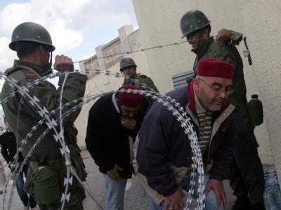In Tunis lassen Soldaten Zivilisten passieren: Spekulationen über eine mögliche Machtübernahme der Armee in Tunesien wies Heereschef Rachid Ammar zurück.