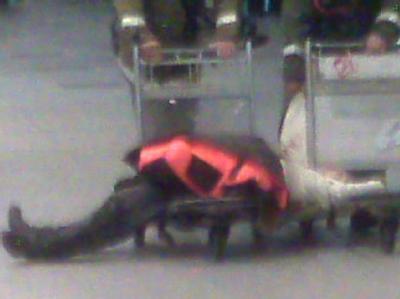 Ein Mensch liegt im Flughafen Domodedowo in Moskau auf einem Gepäckwagen.