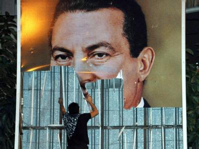 Ein Demonstrant reißt in Alexandria ein riesiges Plakat des ägyptischen Präsidenten Hosni Mubarak ab.