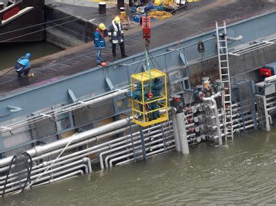 Bergungskräfte begutachten die Rohrleitungen auf dem Oberdeck des auf dem Rhein gekenterten Schwefelsäure-Tankschiffs Waldhof.