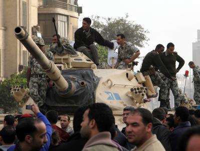 Zahlreiche Panzer haben sich in einer langen Kolonne auf dem Tahrir-Platz aufgestellt. An der Seite stehen gepanzerte Transporter.