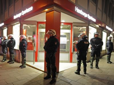 Polizisten bewachen in Hamburg eine Bank im Schanzenviertel. Rund 400 Mitglieder der linken Szene protestierten dort gegen die Zwangsräumung in Berlin.