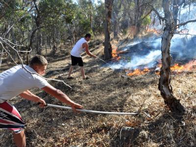 Zwei Australier versuchen die sich ausbreitenden Flammen zu stoppen.