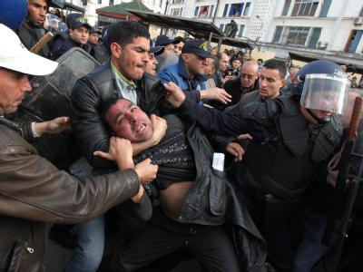 Gewalt in Algier: Polizisten zerren einen Demonstranten von der Straße.