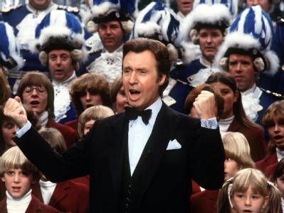Der östereichische Sänger und Schauspieler Peter Alexander singt bei der Aufzeichnung seiner TV-Show im Jahre 1981 mit einem Chor.