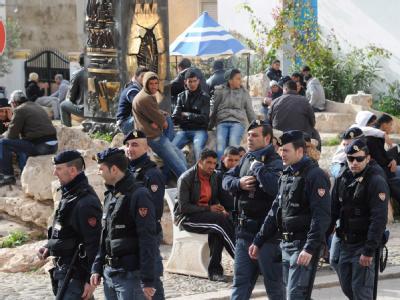 Die italienische Polizei patrouilliert vor einer Gruppe tunesischer Flüchtlinge auf der Insel Lampedusa. (Archivbild)