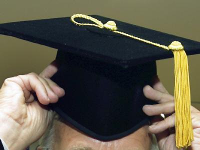 Ein Doktorand setzt sich bei der Titelverleihung den Doktorhut auf. (Archivbild)