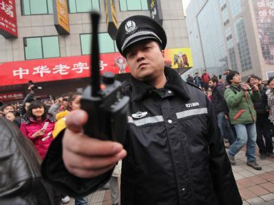 Ein chinesischer Polizist versucht Aufnahmen der Demonstration zu unterbinden.