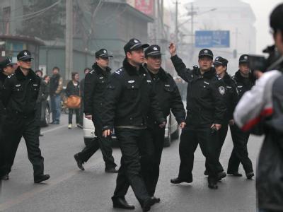 Chinesische Polizisten lösen in Peking eine Menschenmenge auf, nachdem es einen Online-Aufruf zu friedlichen Protestaktionen gegeben hatte.