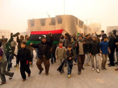 Regierungsgegner in der libyschen Stadt Tobruk halten eine Flage aus der Vor-Gaddafi-Ära bei einer Demonstration hoch.