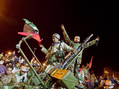 Aufständische ziehen durch das nächtliche Bengasi (Archivbild): Während Gaddafis Truppen mit Luftunterstützung im Kampf gegen Regimegegner Boden gutmachen, kann sich die internationale Gemeinschaft nicht auf die Einrichtung einer Flugverbotszone über Liby