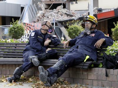 Erschöpft: Zwei Mitarbeiter der Behörde für Zivilverteidigung ruhen sich aus. 70 Menschen konnten nach dem Beben lebend aus den Trümmern gezogen werden.