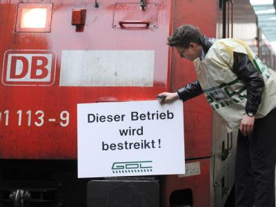 Ein Vertreter der Lokführergewerkschaft GDL lehnt ein Schild mit der Aufschrift «Dieser Betrieb wird bestreikt!» an eine Lok. (Archivbild)